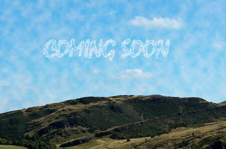 coming soon: Clouds from coming soon in sky. The text coming soon is written using image processing software.  It consists of 3 layers.