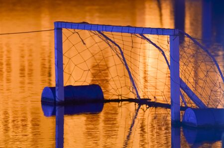 water polo: Meta vacía del water polo flotando en el agua durante la noche.