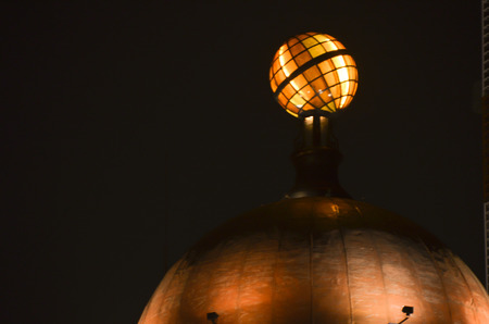 to dominate: A earth rotating on a building top in night. Stock Photo