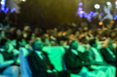 incidental people: A large number of people  and unrecognizable audience at a seminar.