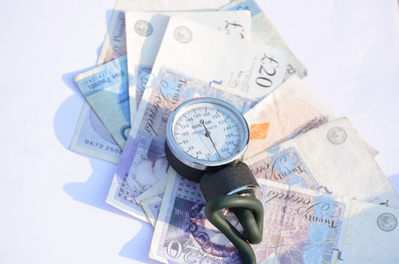 hypertensive: Costs of healthcare withBlood pressure meter. Stock Photo