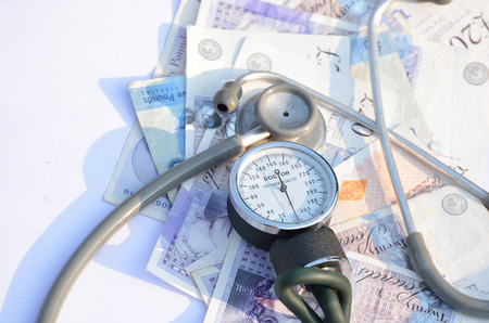 healthcare costs: Costs of healthcare with Blood pressure meter and stethoscope. Stock Photo