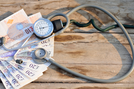 healthcare costs: Costs of healthcare with Blood pressure meter and stethoscope in wooden background. Stock Photo