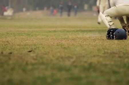 wicket: Boys are playing cricket on Maidan area at Kolkata, India.