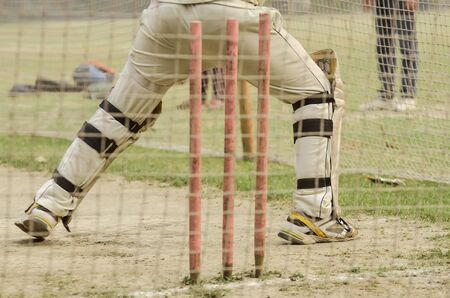 padding: Boy is practicing cricket batting in net. Stock Photo