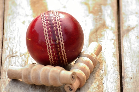bails: Cricket ball and bails with a shadow on a wooden background.