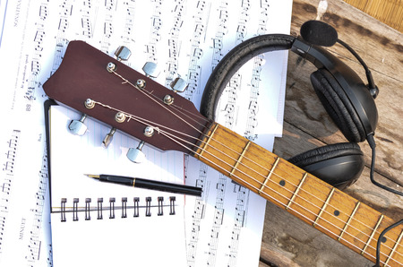 music book: Music book, notepad pen headphone and acoustic guitar on old table.