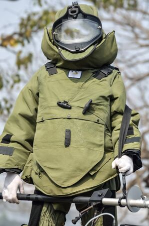 defuse: Young male police in bomb suit used to difuse and disarm explosive bombs.