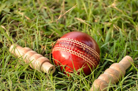 bails: Red leather cricket ball and bails on grass Stock Photo