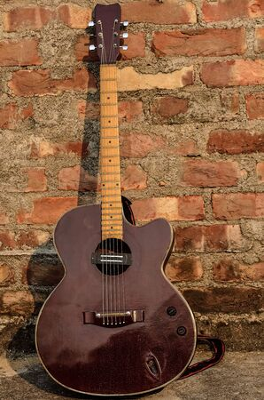 arts culture and entertainment: Acoustic Guitar guitar over brickwall Stock Photo