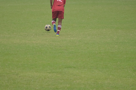 Boy is playing soccer in a ground.Boy is going to kick a soccer ball.
