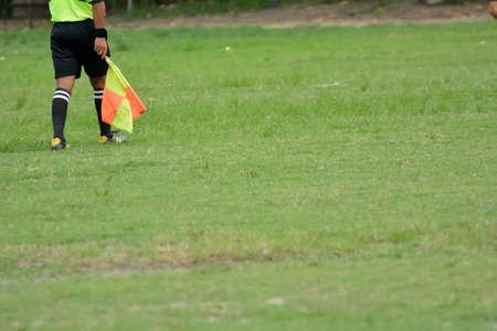 arbitro: Fútbol árbitro asistente se ejecuta con la bandera. Editorial