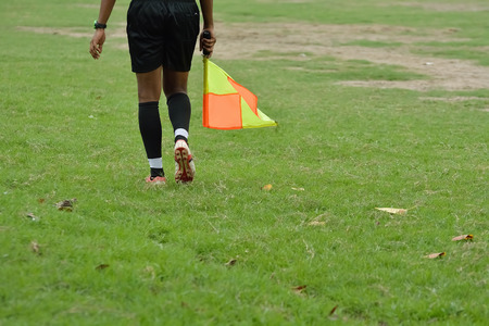 linesman: Soccer assistant referee is running with flag. Stock Photo