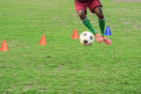 Soccer players practicing dribbling.