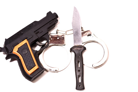 knife, gun and hand lock up on isolated white