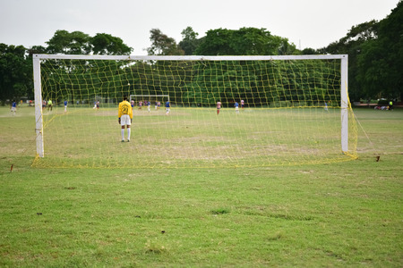 goalline: Boys are playing soccer. Photograph is taken behind the goal.