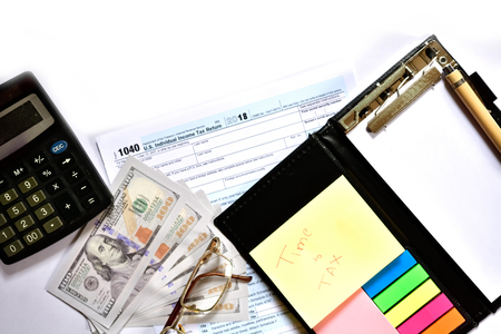 Tax form with notepad, pen and calculator on table