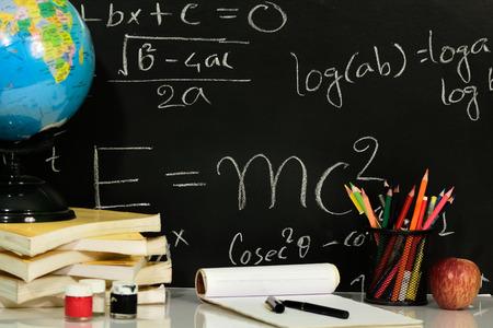 Boeken zijn gestapeld op tafel met wiskundige vergelijkingen op bord Stockfoto - 100369341