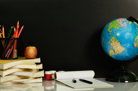 Books are stacked on table against blackboard Stock Photo