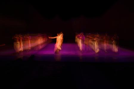 A group of people dancing on stage against dark black