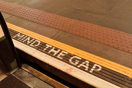 Mind the gap sign on London underground platform.