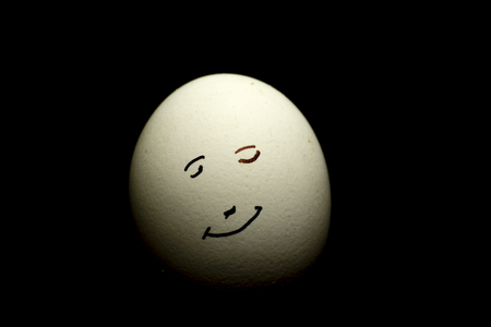 Egg represents human face isolated against black background Banco de Imagens