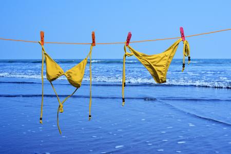 Bikini Hanging sunlight for dry in a sea beach 版權商用圖片