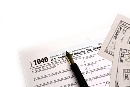 Completing US tax return form 1040 on white background