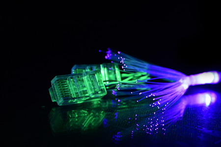 Network cable with fiber optics light on black background