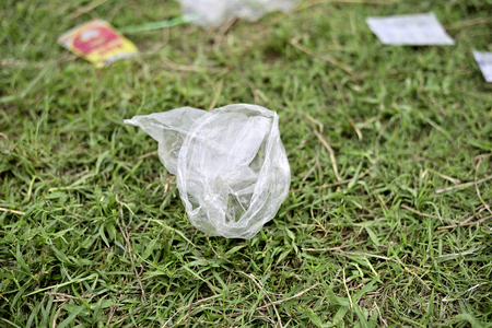 Waste Plastic packets are dumped on green grass field