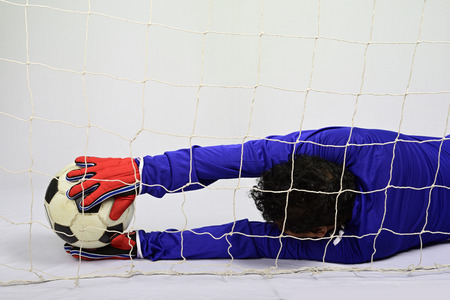 Soccer goalkeeper save to scoring goal against gray background