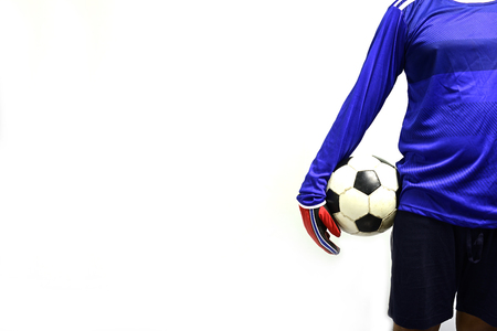 Soccer goalkeeper standing with soccer ball to play against grey background. 免版税图像