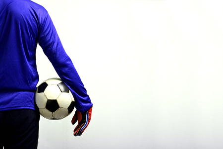 Soccer goalkeeper standing with soccer ball to play against grey background. Imagens