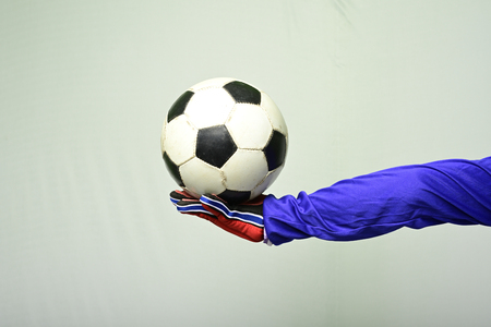 Soccer goalkeeper offer ball to play against white background