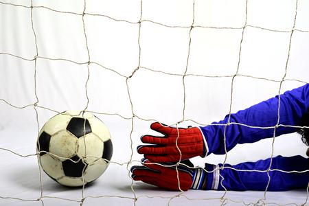 Soccer goalkeeper try to save to scoring goal against gray background 免版税图像