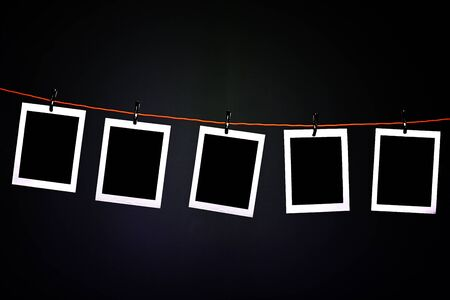 Blank photographs hanging on a rope in photography dark room