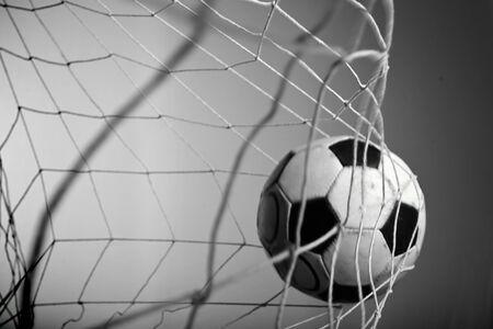 Gol de puntuación, balón de fútbol en la red sobre fondo gris. Foto de archivo