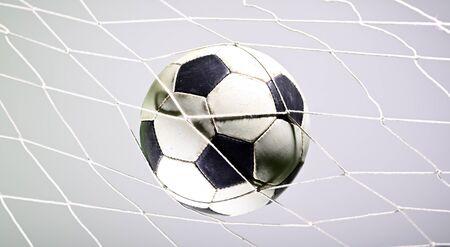 Scoring goal, Soccer ball in the net against gray background.
