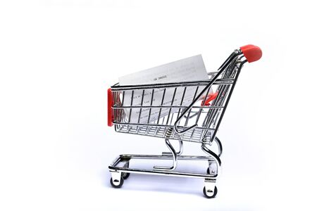 Shopping cart with receipt isolated on white background. Concept of grocery expenses and consumerism.