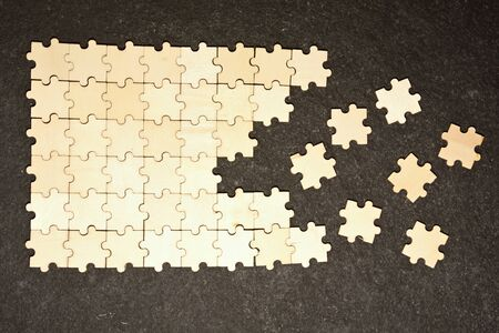 Half ordered puzzle with white jigsaw pieces. One side of the image shows part of the completed puzzle, other side shows the work in progress on a texture black background.