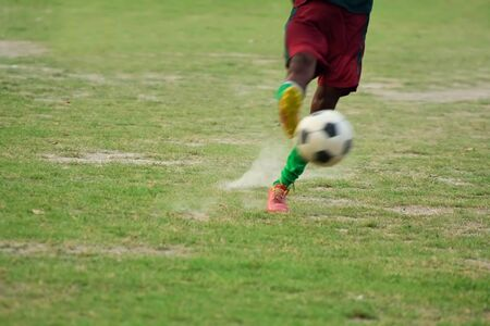 Soccer player is kicking ball during football practice in field Stock Photo