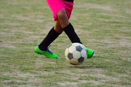 Soccer player is kicking ball during football practice in field