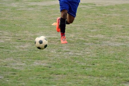 Soccer player is running to kick soccer ball during football practice in field
