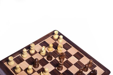 Top angle shot of chess pieces on chessboard against white background. Wooden chess pieces.