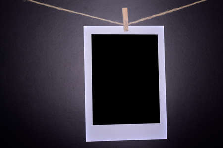 Close-up of blank photographs hanging on a clothesline in darkroom. Stock Photo
