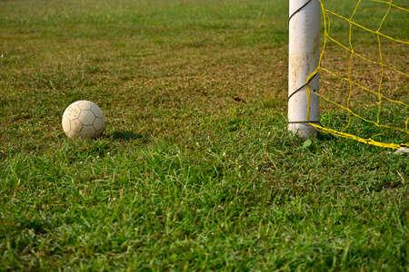 Soccer ball lying on the green grass beside the soccer goal