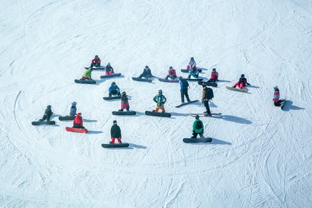 Lots of skiers and snowboarders have a rest on a slope at ski resort. View from above Stok Fotoğraf
