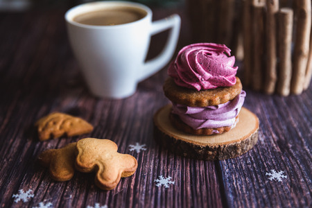 Close up of homemade pink and purple zephyr or marshmallow in powdered sugar with white mug on wooden. Black currant, blueberry marshmallows. Christmas or New Year composition. Christmas card.
