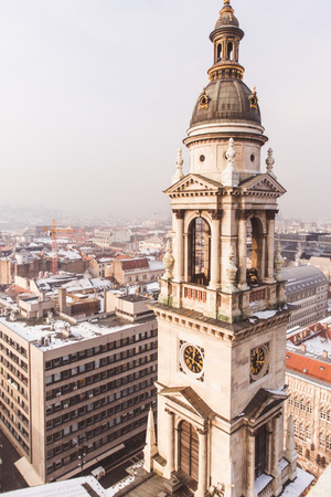 View of Budapest from St. Stephens Basilica, Budapest, Hungary on a snowy foggy day. Snow lies on the roofs of houses