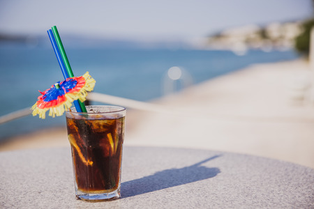 Cold glass of Malibu Cola stand on table near the sea. Summer shine